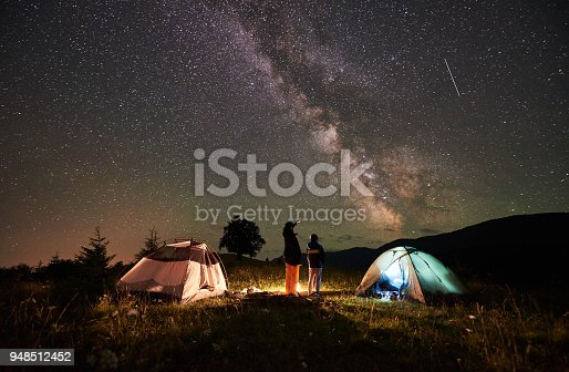 Back view mother and son tourists resting at camping in mountains, standing beside campfire and two tents, looking at night sky full of stars and Milky way, enjoying night scene. Woman pointing at sky