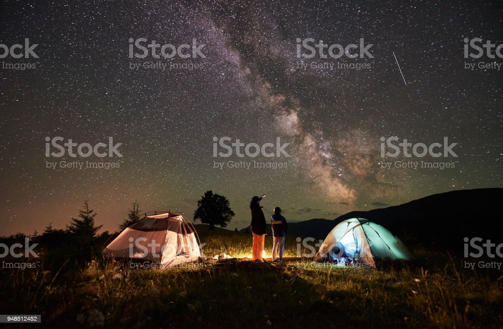 Mother and son tourists resting at camping in mountains at night sky full of stars and Milky way stock photo