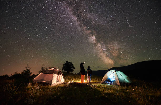 mother and son tourists resting at camping in mountains at night sky full of stars and milky way - camping stock photos and pictures