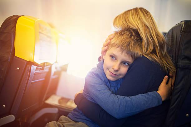 mother and son travelling by plane - sanft und sorgfältig stock-fotos und bilder