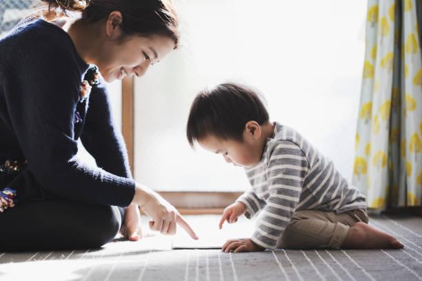 母と息子が一緒にデジタル タブレットを使用して - 子供時代 ストックフォトと画像