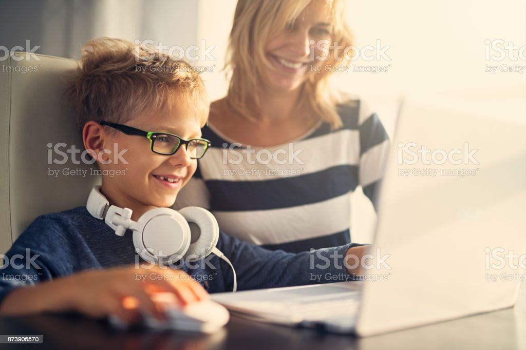 Mother and son using computer together stock photo
