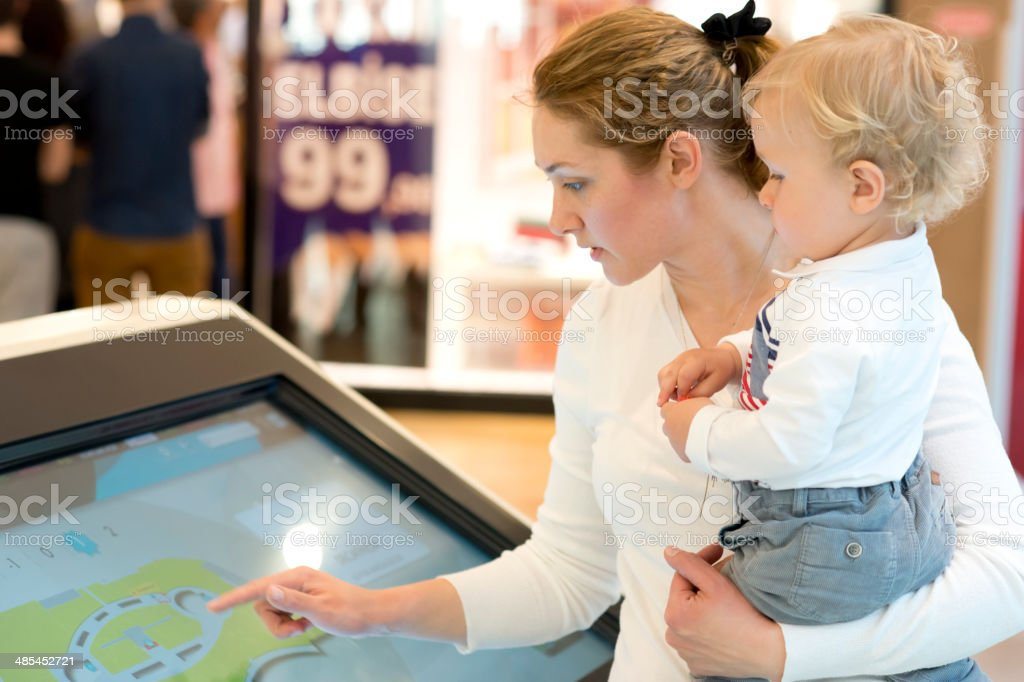 Mother and son using information display stock photo