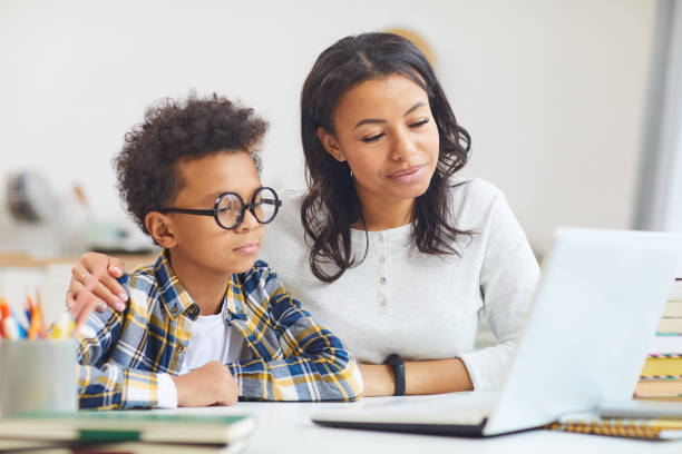 Mother and Son Using Laptop Portrait of cute African boy wearing big glasses while using laptop with mom, homeschooling and remote education concept parent stock pictures, royalty-free photos & images