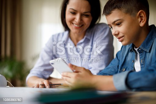 istock Mother and son using mobile phone for homework 1035393782
