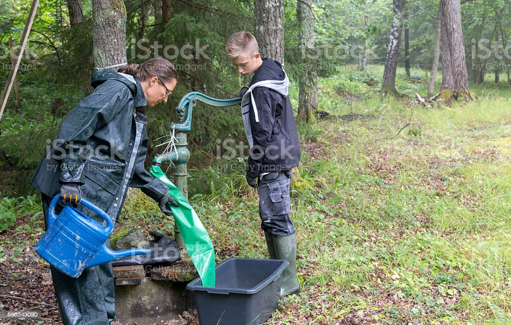 Mother and son using old hand pump. Rainy meadow, Sweden royalty-free stock photo
