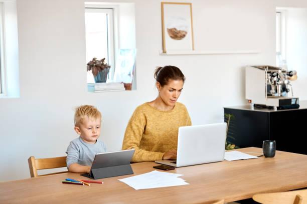 moeder en zoon die technologieën thuis gebruiken - onschuld stockfoto's en -beelden