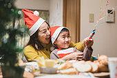 自宅でクリスマスパーティーでポッパーを使用して母と息子