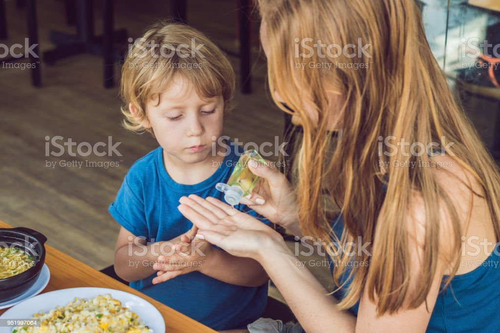 Mother and son using wash hand sanitizer gel in the cafe stock photo