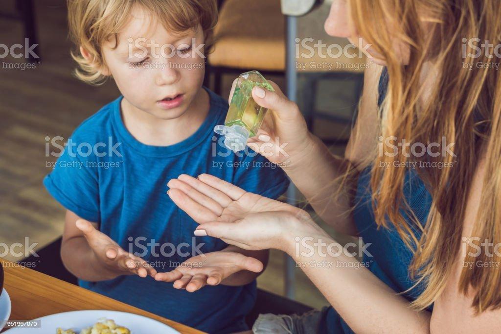 母と息子の洗浄ハンドサニタイザーを使用してゲルのカフェで - ウイルスのロイヤリティフリーストックフォト