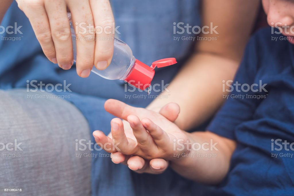 Mother and son using wash hand sanitizer gel stock photo