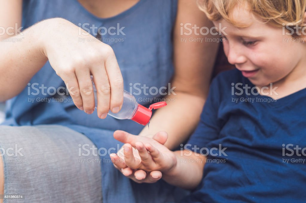 Mother and son using wash hand sanitizer gel pump dispenser stock photo