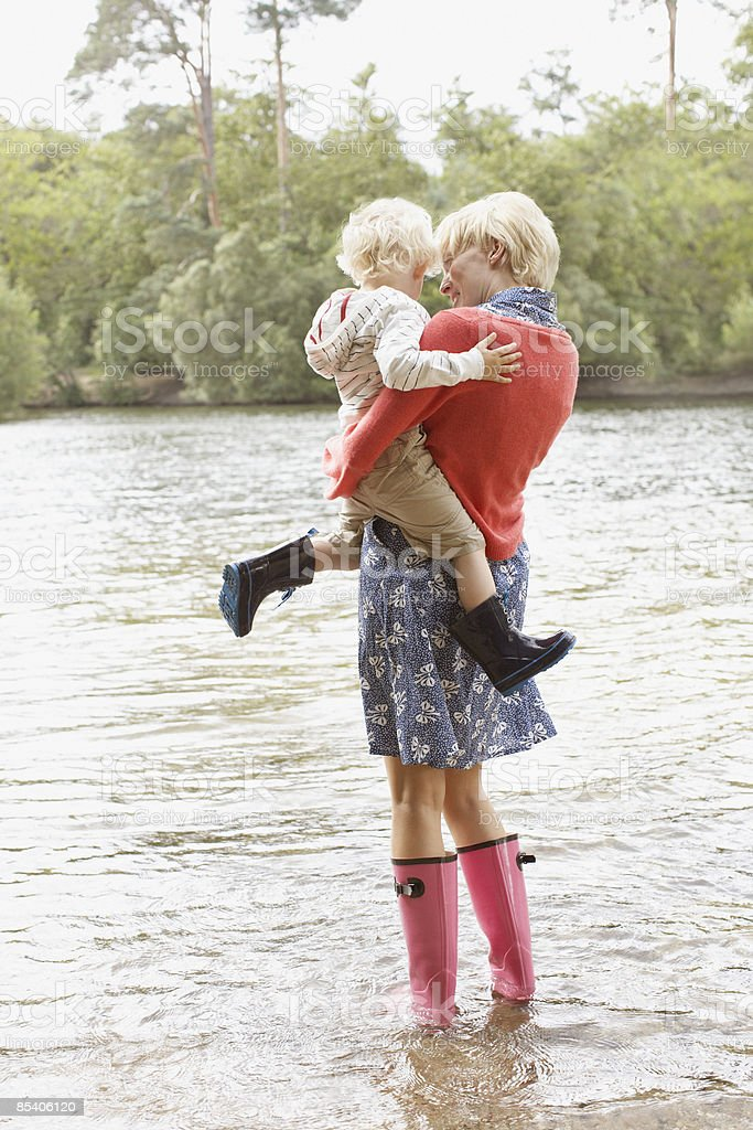 Mother and son wading in lake royalty-free stock photo