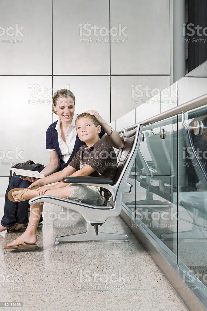 Espera de uma mãe e filho em um terminal de aeroporto foto de stock royalty-free
