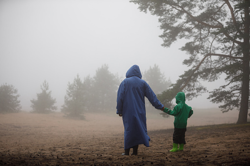 Mother and son walk along the foggy shore. A woman with a boy in raincoats in nature