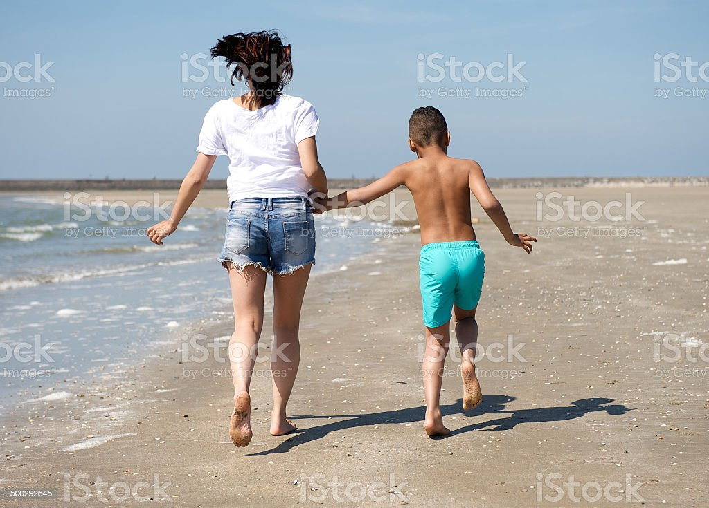 Mother and son walking barefoot stock photo