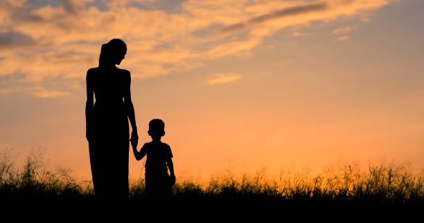 Mother and son walking in the field at sunset.