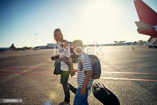 Mother and son getting ready to board the plane. They are holding hands and walking on airstrip. Nikon D850