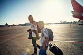 Mother and son getting ready to board the plane. They are holding hands and walking on airstrip.\nNikon D850