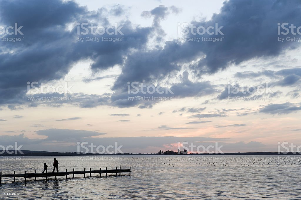 Mother and son walking on lakeside jetty after sunset (XXL) royalty-free stock photo