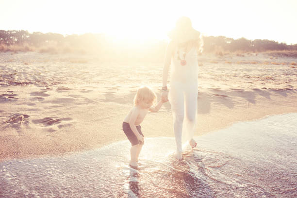 Mother and son walking on the beach stock photo