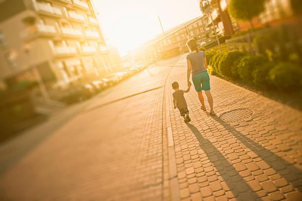 mother and son walking - walking home sunset street bildbanksfoton och bilder