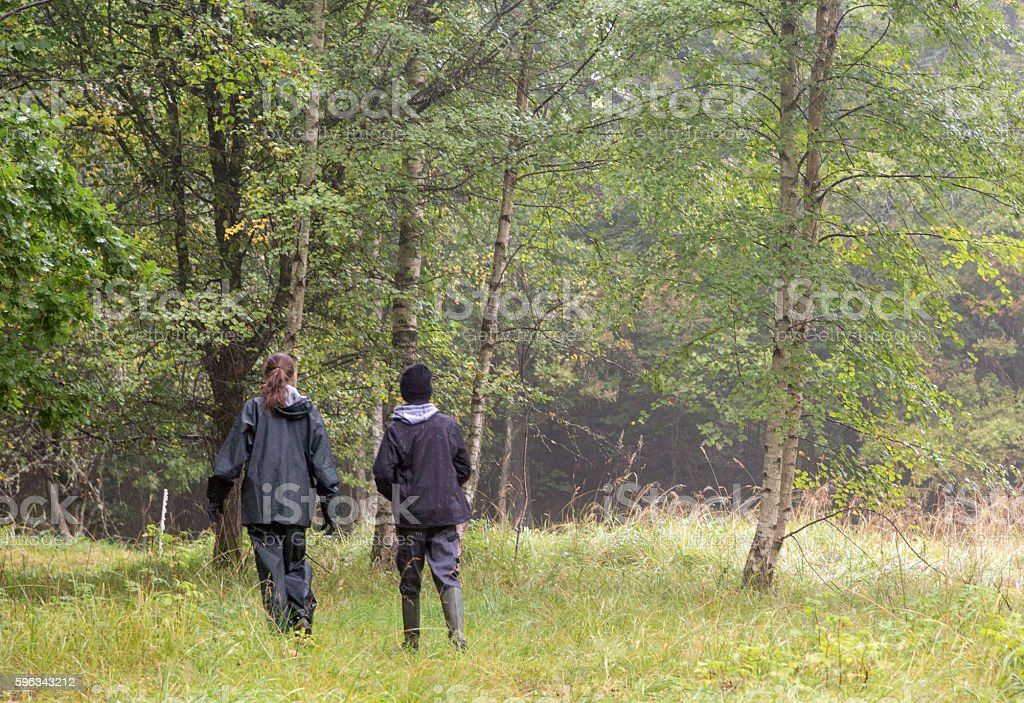 Mother and son walking through rainy meadow, Sweden royalty-free stock photo
