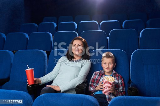 istock Mother and son watching movie in cinema. 1147577763
