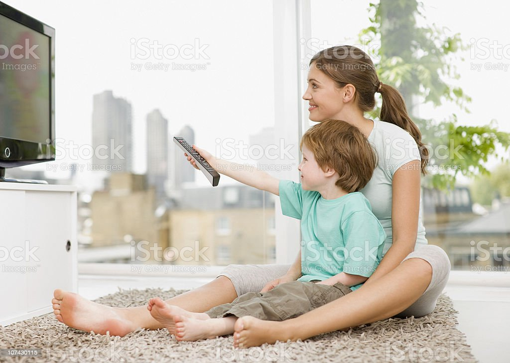 Mother and son watching television stock photo