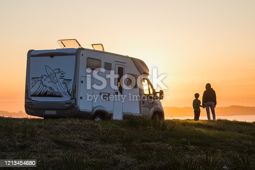 istock mother and son watching the sunset with their motor home at the edge of the sea 1213454680