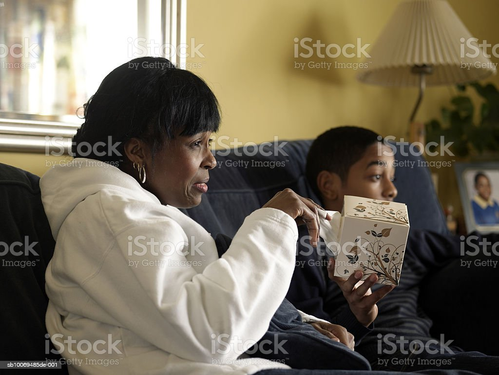 Mother and son (12-13) watching tv together, mother crying royalty-free stock photo