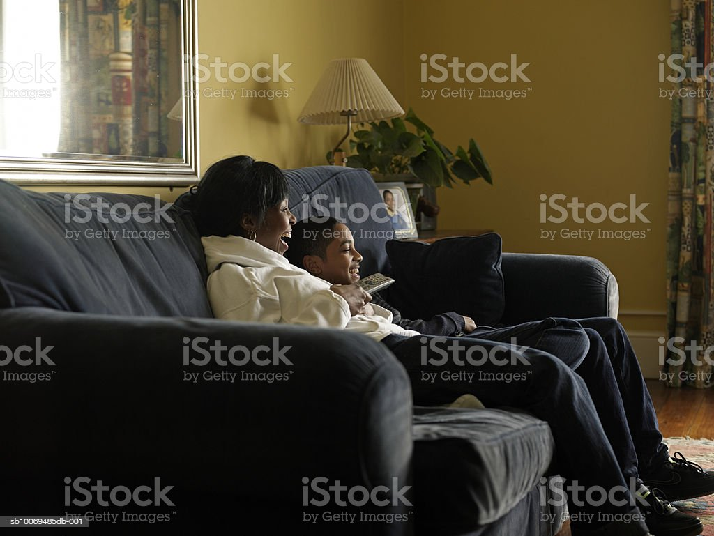 Mother and son (12-13) watching tv together sitting on sofa royalty-free stock photo