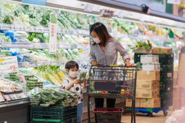 Mother and son wearing face masks shopping together in a supermarket Mother and son wearing face masks shopping together in a supermarket. Okayama, Japan allergy stock pictures, royalty-free photos & images