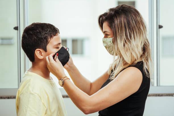 Mutter und Sohn tragen Schutzmaske zu Hause. Coronavirus COVID-19 Prävention. – Foto