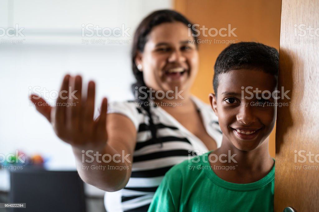 Mother and son welcoming and opening door stock photo