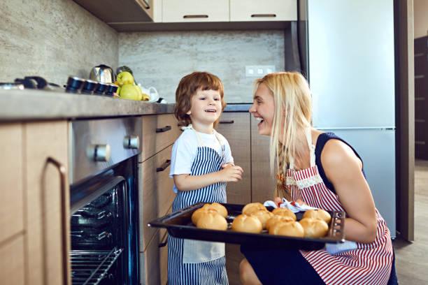 Mutter und Sohn mit einem Tablett mit Blättern aus dem Ofen – Foto