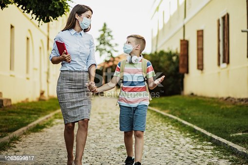 Mother takes her son to school, they are wearing face masks
