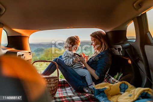 Happy family of mother and son going on a car trip in summer. Photo of mother and son sitting on a blanket at luggage carrier during a summer sunset. Mother and baby son sitting in a car before going on vacations or picnic.