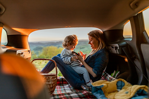 istock Mother and son with pad during car travel at night 1146888147
