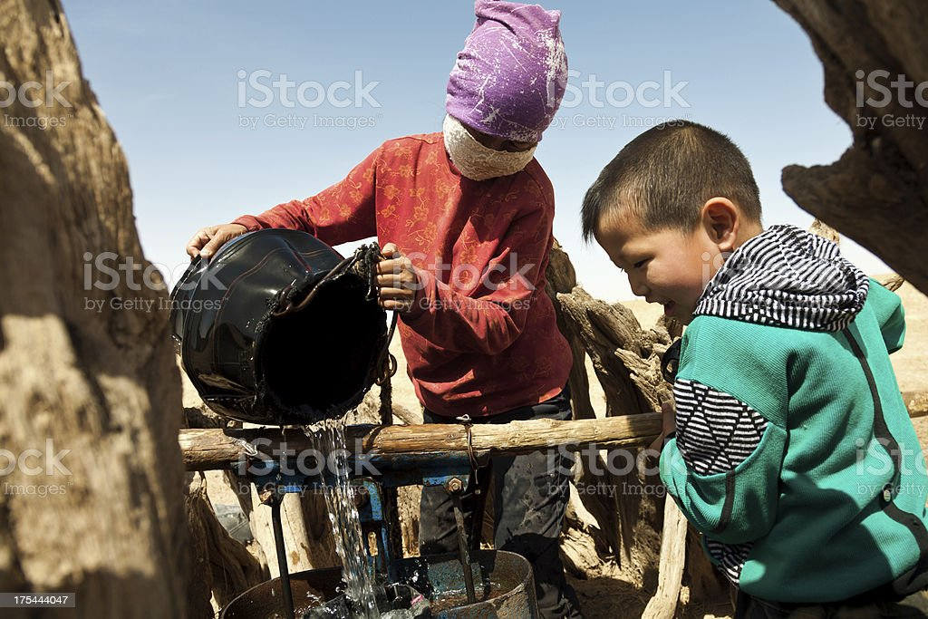 mother and son working in the extraction of water stock photo