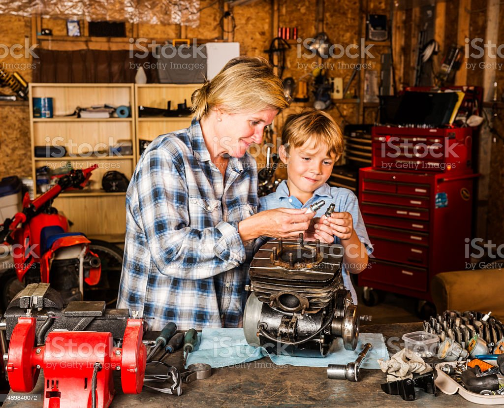 Mother and son working on motorcycle engine in their garage stock photo
