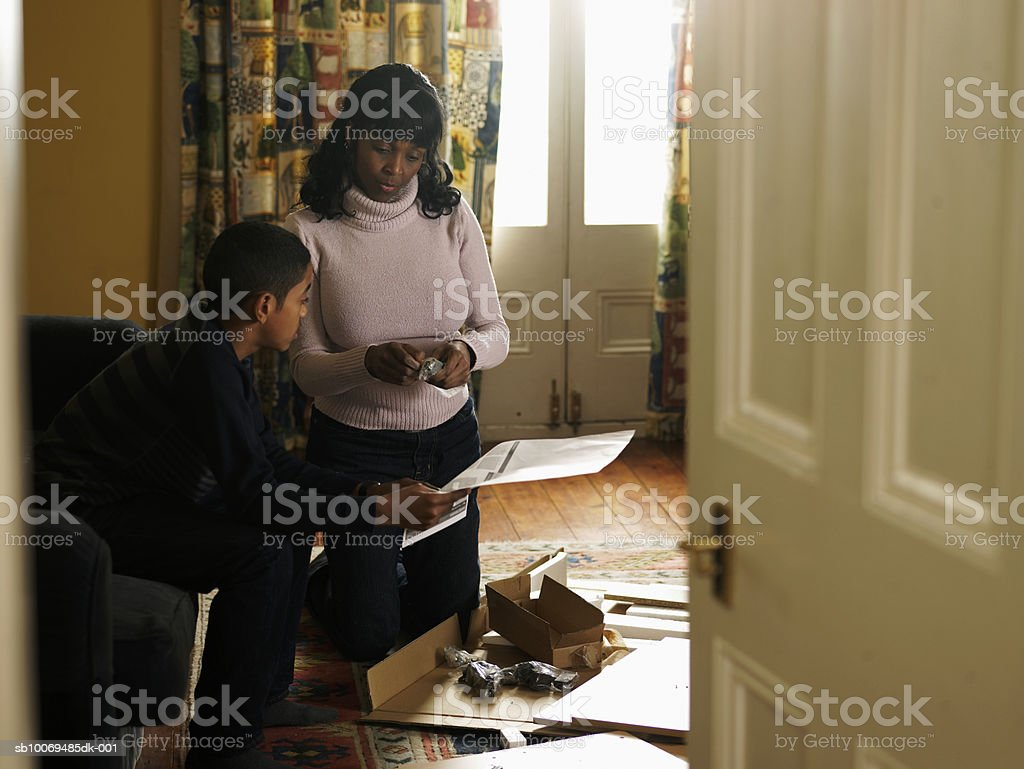 Mother and son (12-13) working together in living room, boy holding instruction manual royalty-free stock photo