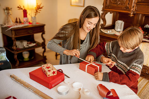 Mother and Son wrapping Christmas Gifts stock photo