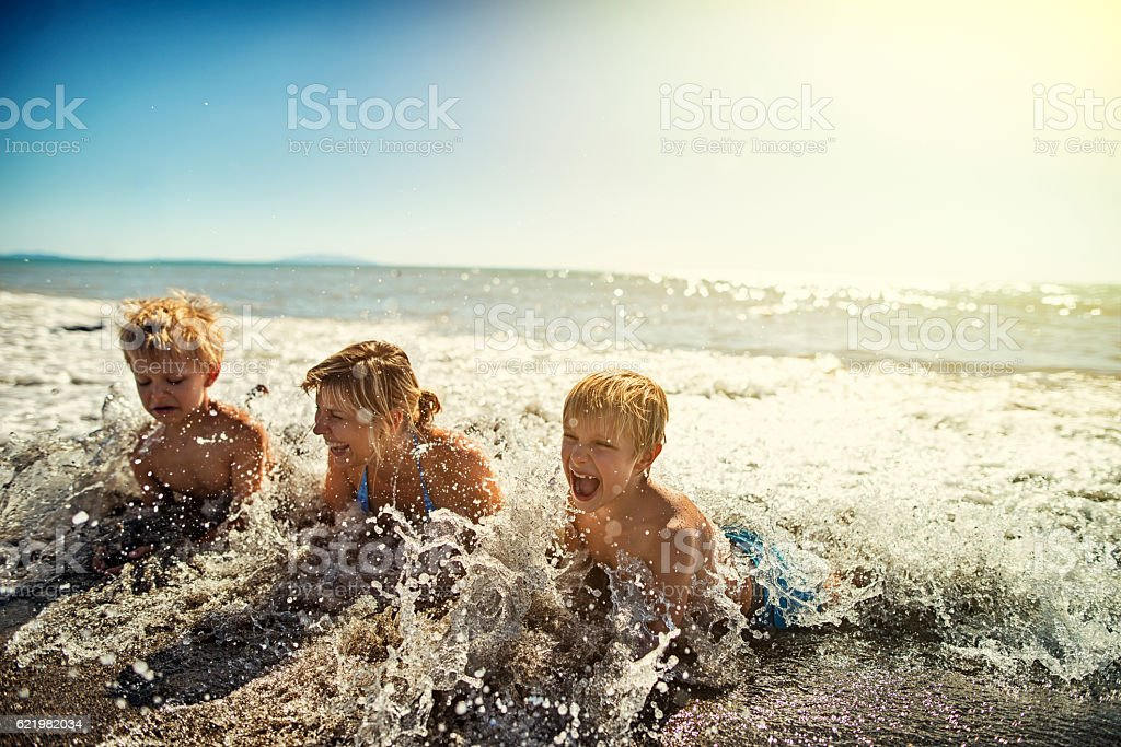 Mother and sons lying on beach splashing in sea waves stock photo