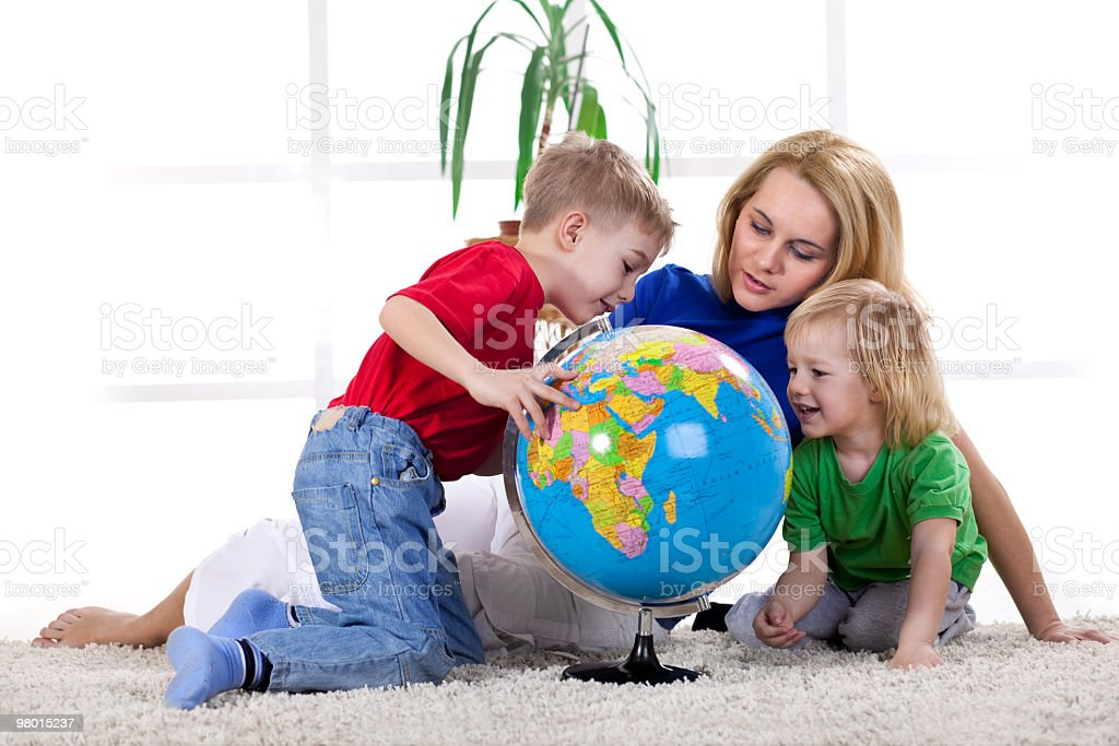Mother and sons playing with the globe royalty-free stock photo
