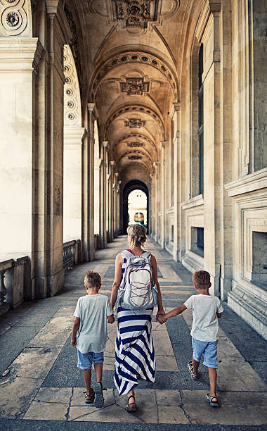 Mother and sons visiting Paris Mother and two sons walking in Paris archway outside of the Louvre Museum. Paris, France. musee du louvre stock pictures, royalty-free photos & images