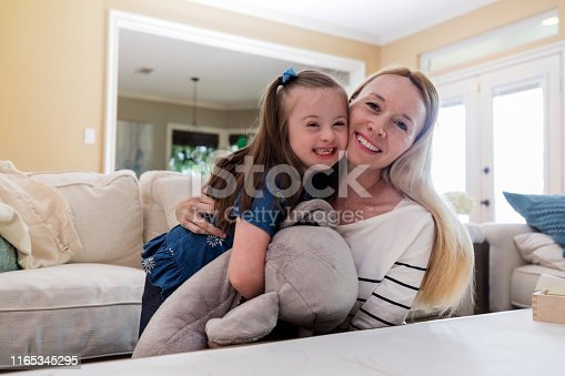 A mid adult mother and her special needs daughter hug each other and look at the camera.