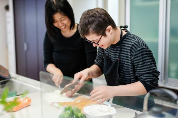 一緒に食事を準備する異なる能力を持つ母と10代の息子 - disabilitycollection ストックフォトと画像