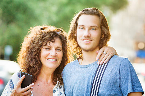 Mother and teenaged son Summer urban portrait with phone stock photo