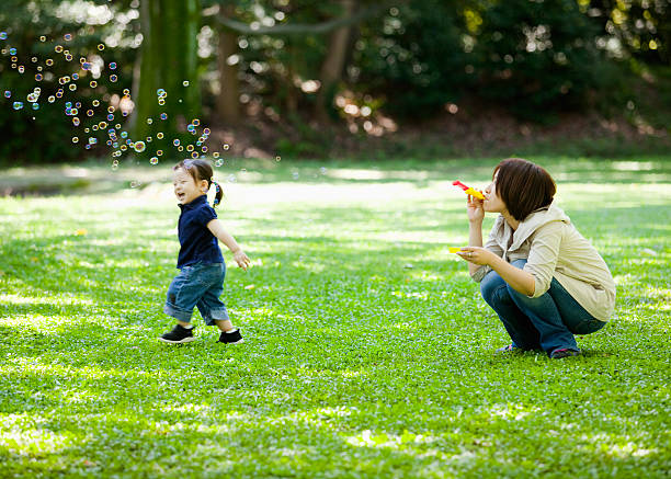 Mother and the daughter playing in a park stock photo